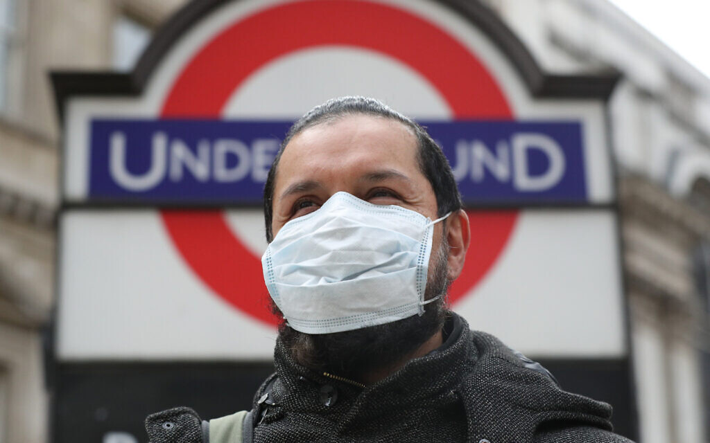 A person wearing a face mask in front of an underground sign in London.