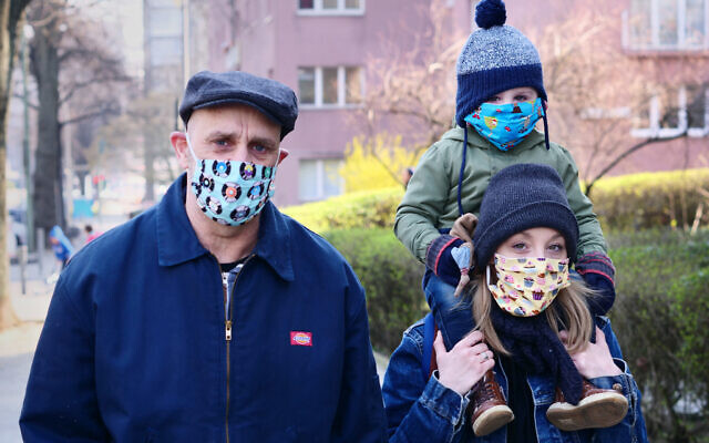 A family goes for a walk in Berlin in colorful masks as protection against the coronavirus.