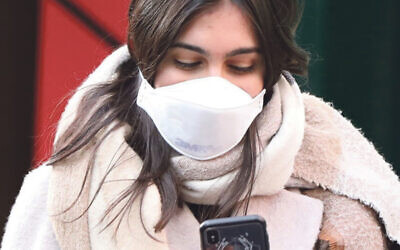 A pedestrian in London wears a protective face mask