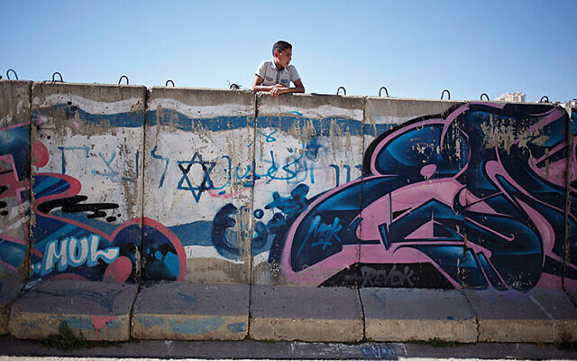 A Palestinian boy looks behind a wall separating Jewish part and Palestinian part of the West Bank. (AP Photo/Ariel Schalit)