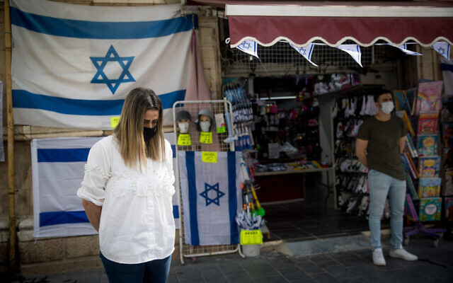 Israelis wearing protective masks due to the COVID-19 pandemic stand in silence in Jerusalem on April 21, 2020 as sirens wail across Israel for two minutes marking the annual day of remembrance for the six million Jewish victims of the Nazi genocide.  Photo by: JINIPIX