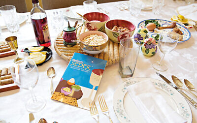 Passover Seder plate and Haggadah on traditionally set table with several side dishes