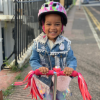 "Three year-old Siena Sendama, pictured, drove 5km on her scooter, having learnt to do so the week before, to raise money for GIFT ""because some people don't have the things that they need."""