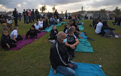 Muslim worshippers some wearing protective face masks gather for Eid al-Fitr prayers marking the end of the holy fasting month of Ramadan at a park in the mixed Arab Jewish city of Jaffa, near Tel Aviv, Israel, Sunday, May 24, 2020. (AP Photo/Oded Balilty)