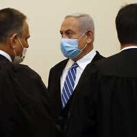 Israeli Prime Minister Benjamin Netanyahu, center, wearing a face mask in line with public health restrictions due to the coronavirus pandemic . (Ronen Zvulun/ Pool Photo via AP)