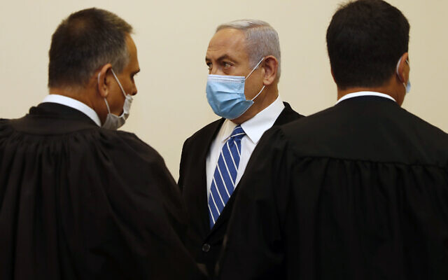 Israeli Prime Minister Benjamin Netanyahu, center, wearing a face mask in line with public health restrictions due to the coronavirus pandemic, stands with his lawyers inside the court room as his corruption trial opens at the Jerusalem District Court, Sunday, May 24, 2020.  . (Ronen Zvulun/ Pool Photo via AP)