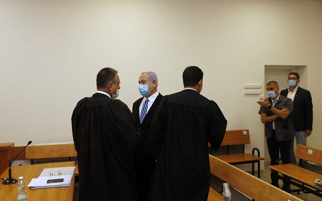 Israeli Prime Minister Benjamin Netanyahu, wearing a face mask in line with public health restrictions due to the coronavirus pandemic, center, stands inside the court room with his lawyers  as his corruption trial opens at the Jerusalem District Court, Sunday, May 24, 2020.  He is the countryÕs first sitting prime minister ever to go on trial, facing charges of fraud, breach of trust, and accepting bribes in a series of corruption cases stemming from ties to wealthy friends. (Ronen Zvulun/ Pool Photo via AP)
