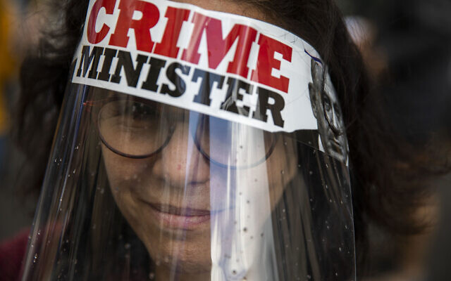 A protester against Israel's Prime Minister Benjamin Netanyahu wears a face mask during a protest outside his residence in Jerusalem, Sunday, May 24, 2020.  . (AP Photo/Ariel Schalit)