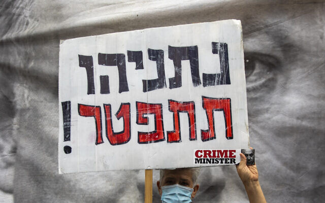 "A protester against Israel's Prime Minister Benjamin Netanyahu holds a placard that reads, ""Netanyahu resign,"" during a protest outside his residence in Jerusalem, Sunday, May 24, 2020.   (AP Photo/Ariel Schalit)"