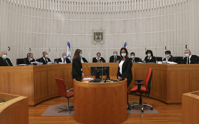 A panel of 11 Israeli Supreme Court judges wearing face masks hear arguments against the legality of Prime Minister Benjamin NetanyahuÕs coalition deal with his former rival, Benny Gantz, at the Israeli Supreme Court in Jerusalem, Monday, May 4, 2020. (Abir Sultan/Pool via AP)