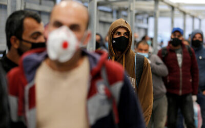 Palestinian laborers head to work in Israel through a checkpoint amid concerns about the spread of the coronavirus disease (COVID-19), near Hebron in the West Bank May 3, 2020. REUTERS/Mussa Qawasma
