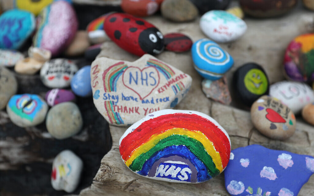 Painted pebbles showing support for the NHS and keyworkers, and containing positive messages