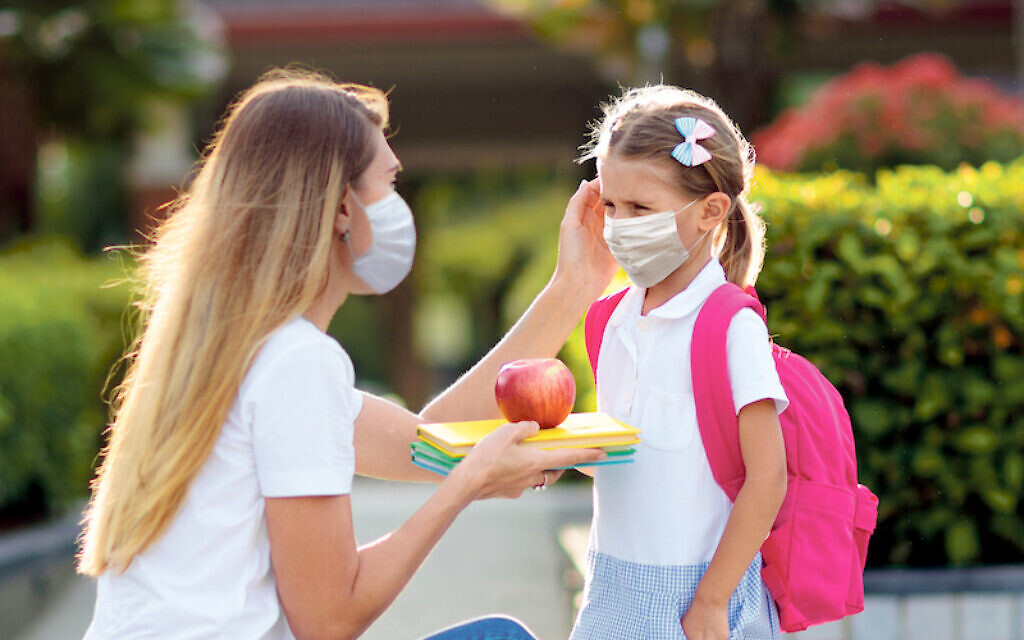 Mother and her child wear masks as students head back to school during the pandemic