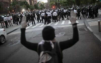 A protester raises her hands as police start to arrest demonstrators refusing to get off the streets during an imposed curfew while marching in a solidarity rally calling for justice over the death of George Floyd, Tuesday, June 2, 2020, in New York.  . (AP Photo/Wong Maye-E)