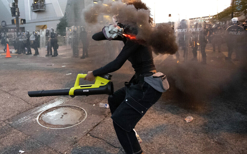 A protester throws a smoke device at police during a protest over the death of George Floyd who died while in police custody, Tuesday, June 2, 2020, in Atlanta. The protests were part of a demonstration against police brutality sparked by the death of George Floyd, a black man who died after being restrained by Minneapolis police officers on May 25. (AP Photo/John Bazemore)