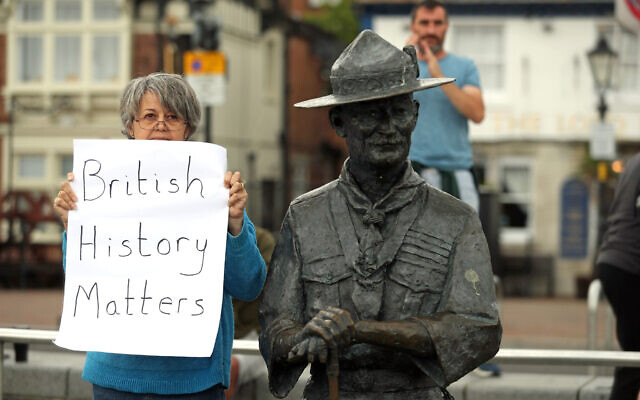A person with a sign protesting 'British History Matters' alongside the statue of Robert Baden-Powell on Poole Quay in Dorset. (Photo credit: Andrew Matthews/PA Wire)
