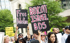 Protestors with signs urging the boycott of Israel