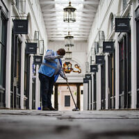 A man cleans social distancing markers in Covent Garden, London as further coronavirus lockdown restrictions are lifted in England. (Credit: Aaron Chown/PA Wire)