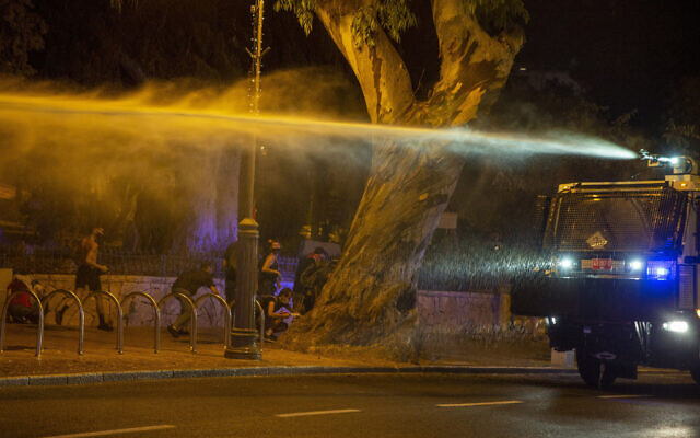 Police use a water cannon to disperse demonstrators during a protest against Israel's Prime Minister Benjamin Netanyahu outside his residence in Jerusalem, early Friday, July 24, 2020. Protesters demanded that the embattled leader resign as he faces a trial on corruption charges and grapples with a deepening coronavirus crisis. (AP Photo/Ariel Schalit)