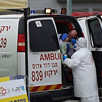 Magen David Adom staff check a young person for Covid-19
