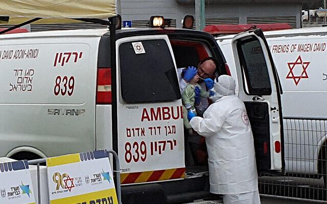 Magen David Adom staff check a young person for Covid-19