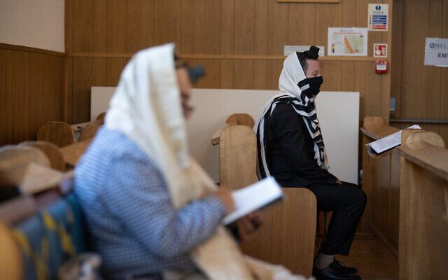 Mill Hill United synagogue's Rabbi Yitzchak Schochet (right) praying under Covid restrictions (Marc Morris)