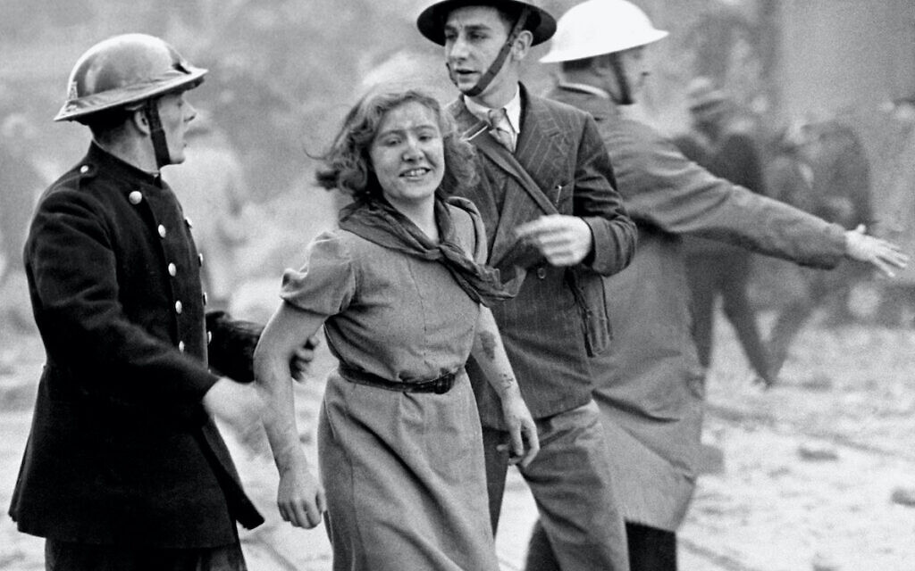 A young woman still smiling after being rescued from a London building just wrecked by a bomb dropped by a daylight German Luftwaffe raid.