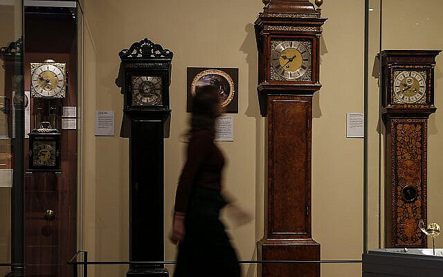 A woman walks past grandfather clocks on display at the Clockmakers' Museum, part of the Science Museum in London.