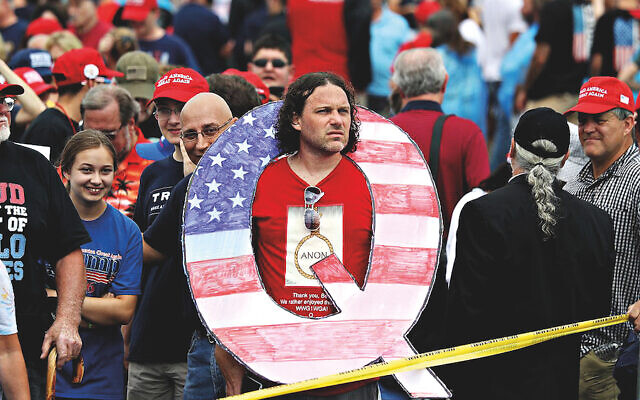 A President Trump supporter wears a giant Q at a political rally