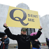 A woman holds a QAnon sign at a protest in Washington, DC