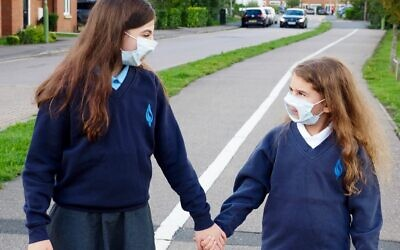 Sisters on their way to school with transparent face-masks