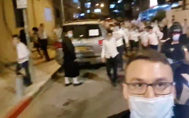 In Bnei Brak, Israel, reporter Ittai Shickman films himself chased by a mob of Charedi Jews while standing outside the home of a prominent rabbi. (Screen shot from Twitter via JTA)