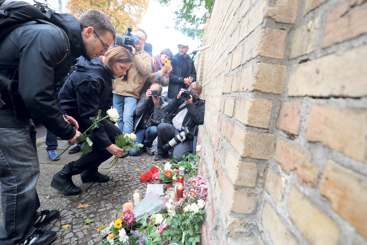 People leave flowers and candles in memory of the victims of the attack in Halle, Germany