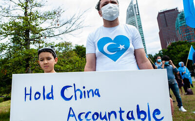 A man and his child holding a placard against China during the demonstration.   (Photo by Ana Fernandez / SOPA Images/Sipa USA)