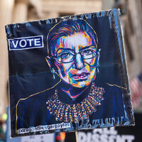 A protester holds up a sign with an image of the late Supreme Court Judge Ruth Bader Ginsburg as a few hundred demonstrators protest the Supreme Court nomination of Judge Amy Coney Barrett on Wall Street in New York City on October 17, 2020. (Photo by Gabriele Holtermann/Sipa USA)