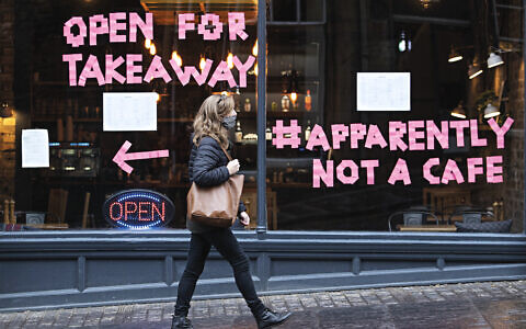 A woman walks past a cafe after a range of new restrictions to combat the rise in coronavirus cases came into place