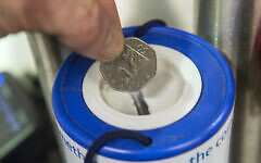 A coin is dropped into a charity collection container