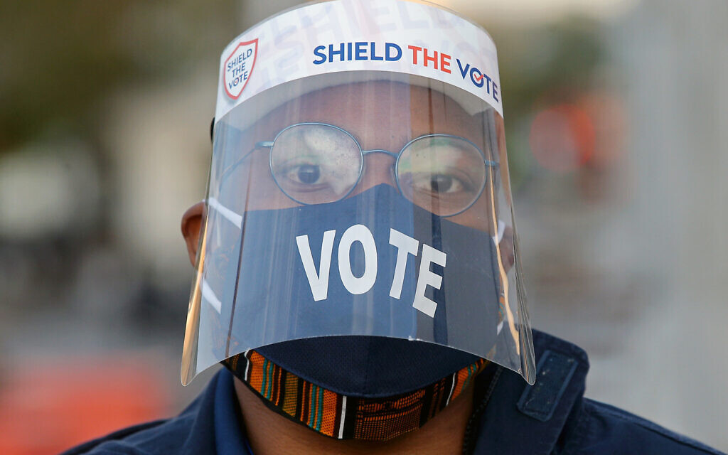 A voter wears a face mask and a face shield outside a polling station on Election Day during the 2020 general elections. Yegor Aleyev/TASS