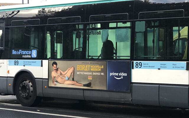 A RATP bus with a billboard of Sacha Baron Cohen wearing a ring with the word Allah on it moves through Paris, France on Nov. 2, 2020. (Courtesy of @firehairedreamr/Twitter via JTA)