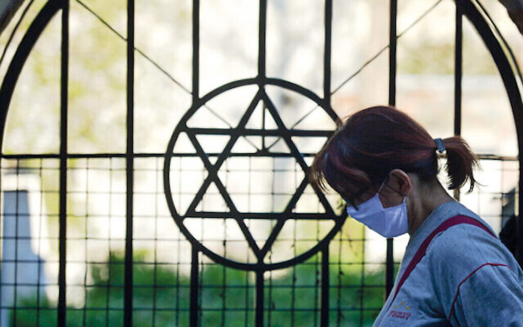 A masked woman passes by the Star of David outside a shul. Jewish communities have been disproportionately affected by the virus. (Photo by Artur Widak/NurPhoto)