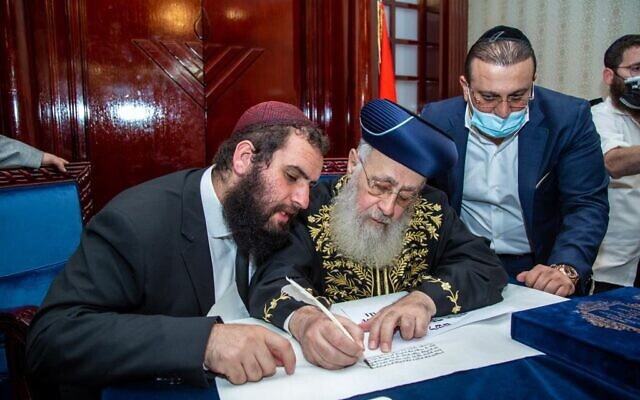 Chief Rabbi Yosef (centre) is joined by Rabbi Levi Duchman (left) as he signs a letter of endorsement for the community.    (Photo credit: Dubai Jewish Community Centre / Courtesy)