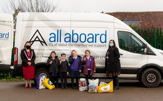Youngsters (pictured with headteacher Rita Alak-Levi and deputy headteacher Lisa Wolf) at Hertsmere Jewish Primary School enjoy their doughnuts, which were sponsored by All Aboard as a thank you for a huge collection drive. Credit: Claire Jonas Photography