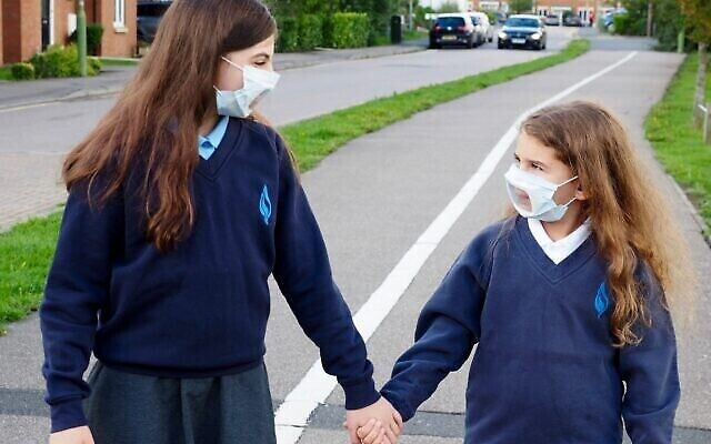 Sisters on their way to school with transparent face masks.