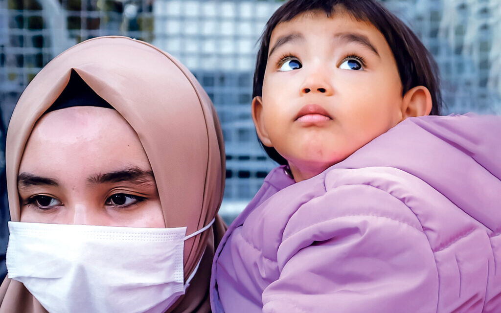 A member of the Muslim Uighur minority holds a child in her arms as she demonstrates in front of the Chinese consulate on December 30, 2020, in Istanbul,  (Photo by BULENT KILIC/AFP via Getty Images)