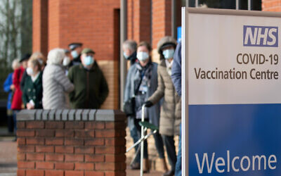People wait to receive their Covid-19 vaccine at an NHS vaccine centre