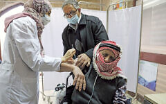 A Palestinian man is helped by his son as he receives a vaccination against the coronavirus disease (COVID-19) as Israel continues its national vaccination drive, in East Jerusalem December 23, 2020. REUTERS/Ammar Awad