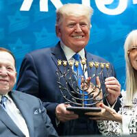 President Donald J. Trump receives a menorah from Miriam and Sheldon Adelson at the Israeli American Council National Summit Saturday, Dec. 7, 2019, in Hollywood, Fla. (Official White House Photo by Joyce N. Boghosian) (Wikipedia/ Source:	President Trump at the Israeli American Council National Summit Author: The White House from Washington, DC / Public domain)