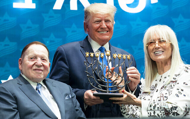 President Donald J. Trump receives a menorah from Miriam and Sheldon Adelson at the Israeli American Council National Summit Saturday, Dec. 7, 2019, in Hollywood, Fla. (Official White House Photo by Joyce N. Boghosian) (Wikipedia/ Source:President Trump at the Israeli American Council National Summit Author: The White House from Washington, DC / Public domain)