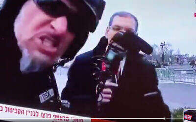 A protestor harasses Israeli journalist Gil Tamari and levels antisemitic slurs. (Screen shot)
