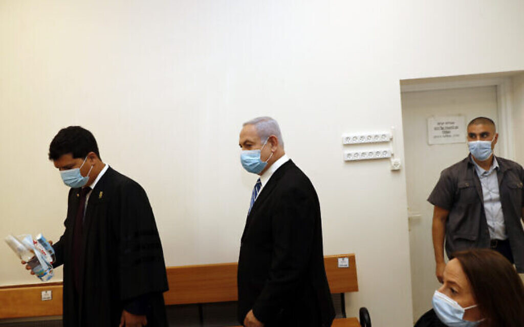 Israeli Prime Minister Benjamin Netanyahu, center, wearing a face mask in line with public health restrictions due to the coronavirus pandemic, enters the court room with his lawyer as his corruption trial opens at the Jerusalem District Court